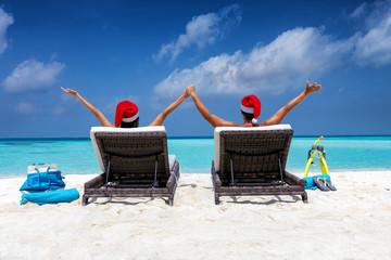 Winterurlaub Konzept: glückliches Paar mit Weihnachtsmützen liegt auf Liegestühlen am tropischen Strand der Malediven
