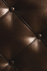 Surface of a rhombic split skin with buttons on the back of the bed. Rhombic patterns of bulk skin brown. Overflowing casing surface