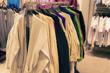 colorful bright pullover hoodies and sweaters hang on hangers in store