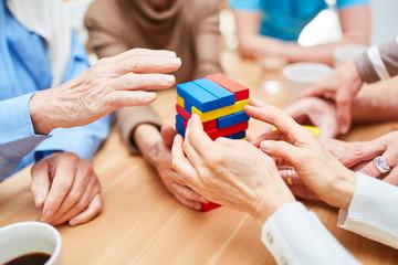 Gruppe Senioren baut Turm aus Bausteinen