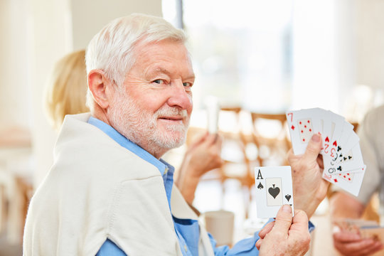 Senior als Rentner beim Karten spielen