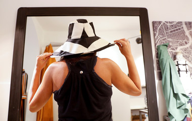A women tries a hat in front of a mirror in a shop in Rome