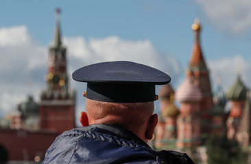 A security guard looks towards the Spasskaya Tower of the Kremlin and St. Basil's Cathedral from a pedestrian bridge over the Moskva river at the Zaryadye Park in central Moscow
