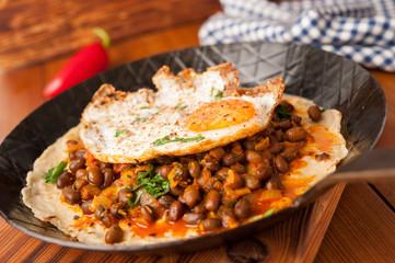 Chili Bohnen auf Tortilla mit Spiegelei in Bratpfanne