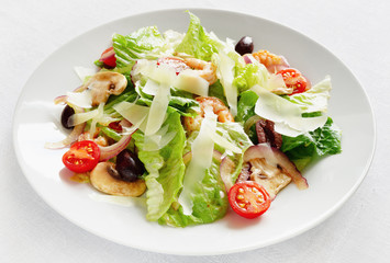 salad with romaine lattuce, scampi, champingons, cherry tomatoes, olives, and red onion dressed with modena vinegar and olive oil and sprinkled with cheese