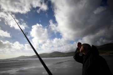 A man participates in the Diawa Irish Pairs sea angling event in windy conditions on the Dingle Peninsula of Inch beach in Inch