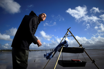 A man untangles his fishing wire during the Diawa Irish Pairs sea angling event in windy conditions on the Dingle Peninsula of Inch beach in Inch