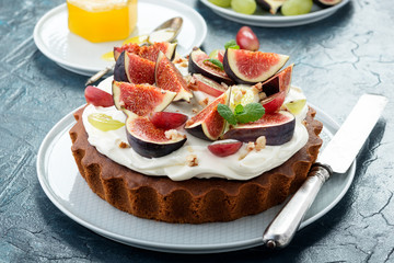 Delicious creamy tart cake with fresh figs and grape.