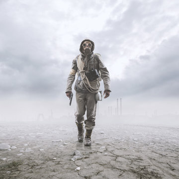 Brave soldier with gas mask walking in a post atomic landscape