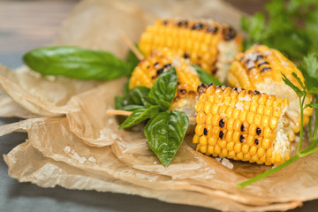 Corn baked in olive oil, with pepper, salt and basil on blue dish on a black stone surface