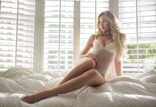 Attractive woman lying down in her bed, wearing white lingerie