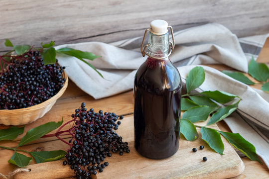 A bottle of black elder syrup with fresh elderberries