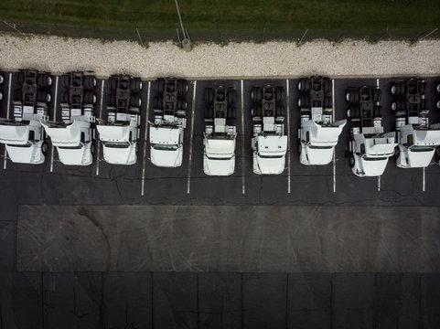 Fleet of white 18-wheeler semi-trucks overhead view drone photography