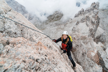young attractive female university student on a steep and exposed rock face climbs a Via Ferrata in Alta Badia in the South Tyrol
