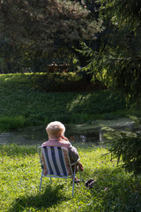Old lady sitting in the chair and calling by phone