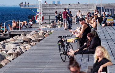 People enjoy warm weather on a pier in Malmo