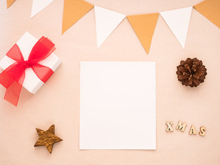 Christmas composition with gift, white paper blank, pine cones, flags. Flat lay, top view, copy space