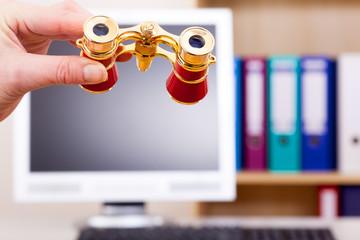 Hand holding binoculars in front of computer screen