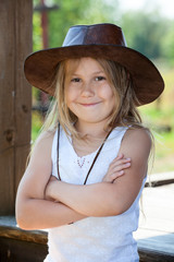 Pretty Caucasian girl standing with crossing hands with leather cowboy hat on head