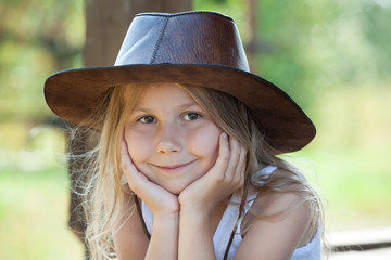 Charming girl in leather cowboy hat portrait, blond hair, brown eyes
