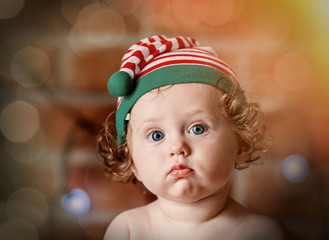Little baby boy in elf hat with Christmas fairy lights on background. Christmas time season image