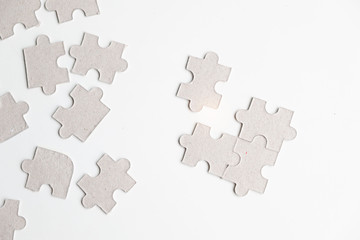 Unfinished white jigsaw puzzle pieces on white background