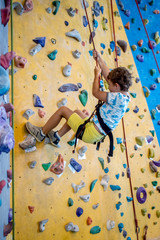 young boy is climbing on artificial climbing wall