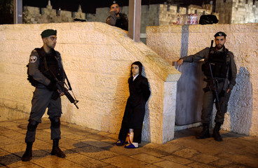 A young Jewish boy stands near Israeli security forces guarding outside Jerusalem's Damascus Gate after a suspected stabbing attack