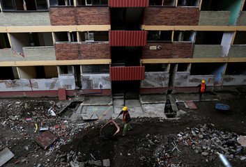 Workers remove debris from the buildings damaged by the devastating earthquake in the Tlalpan neighbourhood, that took place in Mexico City last year