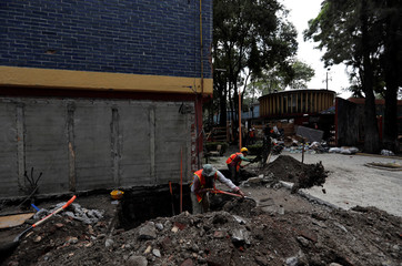 Workers work in the site where buildings were damaged by the devastating earthquake iin the Tlalpan neighbourhood that took place in Mexico City last year