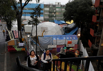 People walk past near the site where building were damaged by the devastating in the Tlalpan neighbourhood, that took place in Mexico City last year