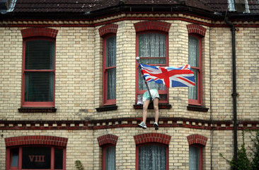The legs of a mannequin hang out of the window of a house on a residential street in Brighton