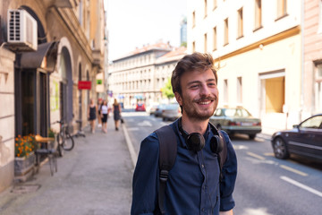 Portrait of cheerful young man waiting on the street