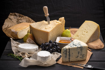 Parmesan, brie, caciotta, camambert and other cheese with pear and honey on wooden table