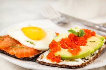Avocado and red caviar, smoked salmon and fried egg rye toasts for breakfast, close up