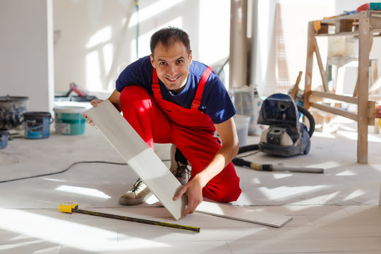 Master is wearing work clothes, is checking horizon of installing tiles, using building level, adjusting, professional repairing work