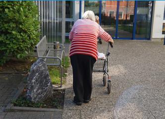 Seniorin mit Rollator auf dem Weg ins Altersheim