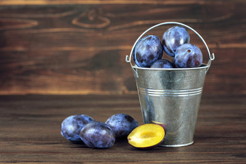 Plums in the bucket on wooden table