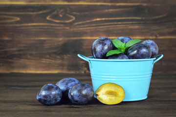 Fresh plums in the bowl  on wooden background