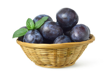 Plums in the basket isolated on white