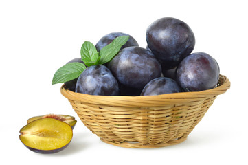 Fresh plums in the basket isolated on white background