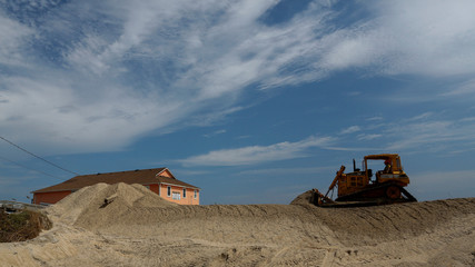 A backhoe removes sand from the street after the pass of Hurricane Florence, now downgraded to a tropical depression in Rodanthe, North Carolina