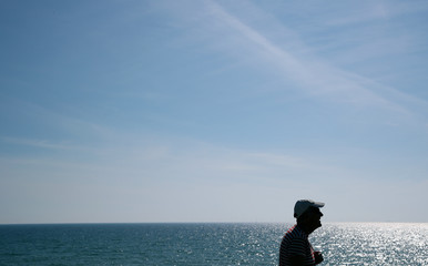 A man wearing a cap walks along the sea front in Brighton