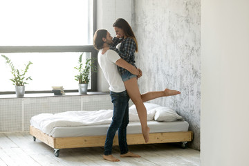 Millennial husband hold young wife in hands enjoying intimacy in bedroom, loving romantic couple hugging near bed, boyfriend lift up happy girlfriend looking each other in eyes, spending time together