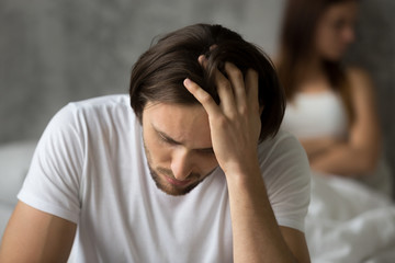 Close up of upset desperate man thinking about relationship problems, worried husband considering break up with beloved girlfriend after cheating, young spouses feel upset after fight or quarrel