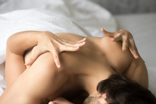 Close up of passionate hot couple have sex feeling ecstasy on white sheets in bedroom, sensual lovers make love in bed reach orgasm or pleasure, satisfied woman embrace man bending hands with desire