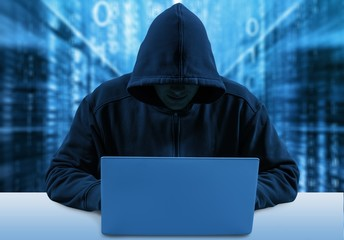 Undefined hacker using computer wearing dark hoodie