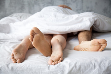 Close up of passionate lovers feet touch having sex on white sheet in bedroom, sensual couple enjoy intimate moment relaxing in bed, legs of boyfriend and girlfriend make love in woman on top position