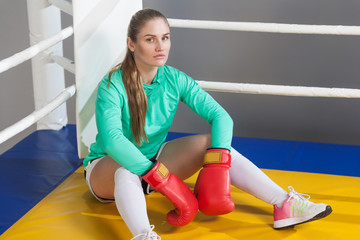 Side view portrait of athletic young woman with collected hair wearing in green long sleeve and red gloves sitting in the corner of boxing ring and take a rest. indoor studio shot. on gray background.