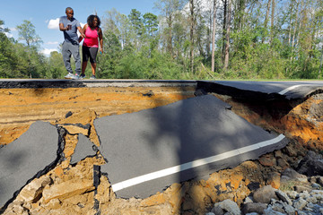 Passersby look at a section of washed-out road damaged by flood waters in the aftermath of Hurricane Florence, now downgraded to a tropical depression, in Currie, North Carolina